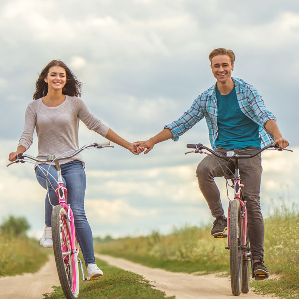 couple-holding-hands-while-riding-bicycles