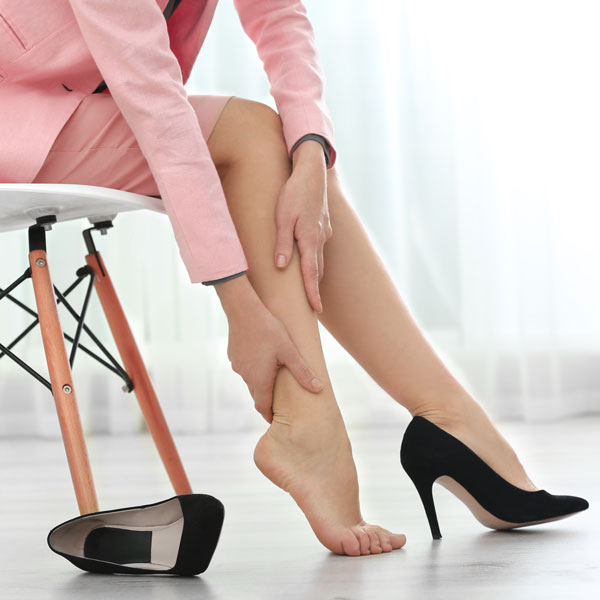 working-woman-holding-aching-legs